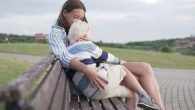 A mamã e o filho estão sentando-se em um banco no parque e no por do sol de espera vídeos de arquivo