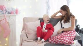 A mamã e o filho estão sentando-se pelo equipamento da árvore de Natal vídeos de arquivo