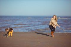 A mamã e o filho estão tirando na areia com as varas Fotos de Stock