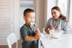 A mamã e o filho fazem a massa para panquecas imagem de stock royalty free