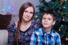 a mamã e o filho felizes comemoram em casa o Natal, o humor do ano novo, a árvore de Natal e os presentes imagem de stock royalty free