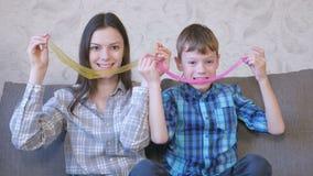 A mamã e o filho felizes estão jogando com o limo que senta-se no sofá Esticando o limo vídeos de arquivo