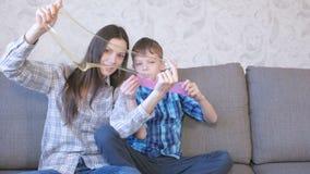 A mamã e o filho felizes estão jogando com o limo que senta-se no sofá Esticando o limo que olha através do limo filme
