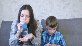 A mamã e o filho inflam bolhas grandes do limos Jogo com limo vídeos de arquivo