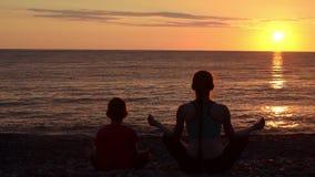 A mamã e o filho meditam sobre a praia na posição de lótus Vista da parte traseira, por do sol, silhuetas video estoque