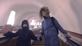 A mamã e o filho na roupa do inverno estão movendo a escada rolante no túnel do metro vídeos de arquivo