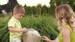 A mamã e o filho pequeno jogam no parque no verão filme