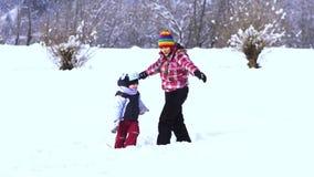 A mamã e o filho pequeno têm o divertimento que joga na neve Riem e caem na neve vídeos de arquivo