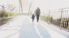 A mamã e o filho pequeno vão sobre a ponte vídeos de arquivo