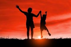 A mamã e o filho que têm o divertimento no por do sol, família uma estadia feliz, criança asiática, mostram em silhueta uma crian fotos de stock royalty free