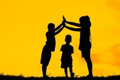 A mamã e o filho que têm o divertimento no por do sol, família uma estadia feliz, criança asiática, mostram em silhueta uma crian imagens de stock