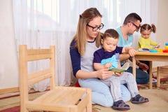 A mamã e o pai leram um livro com as crianças na sala Imagens de Stock