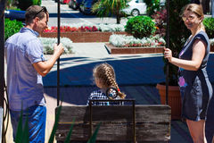 a mamã e o paizinho balançam a filha em um balanço Imagem de Stock Royalty Free