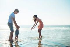 A mamã e o paizinho ensinam o bebê andar Família feliz nova foto de stock