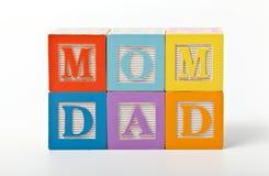 A mamã e o paizinho exprimem escrito com blocos do jogo Foto de Stock