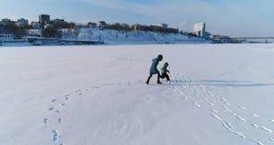 A mamã e o sol são de corrida e de jogo junto na neve Metragem aérea Passatempo da família no inverno vídeos de arquivo