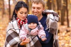 Mamã e paizinho que guardam o bebê nas mãos Fotos de Stock