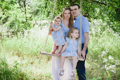 Mamã e paizinho que jogam na natureza e que abraçam duas filhas Imagens de Stock Royalty Free
