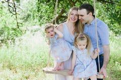 Mamã e paizinho que jogam na natureza e que abraçam duas filhas Imagem de Stock