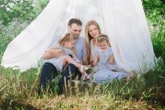 Mamã e paizinho que jogam na natureza e que abraçam duas filhas Imagens de Stock