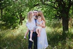 Mamã e paizinho que jogam na natureza e que abraçam duas filhas Foto de Stock