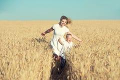 A mamã e pouco filho estão correndo em torno do campo de trigo fotografia de stock royalty free
