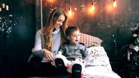 Mamã e rapaz pequeno que leem um livro video estoque