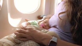 Mamã e seu bebê de sono que viajam pelo plano imagem de stock royalty free