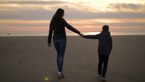 A mamã e seu filho estão andando ao longo do litoral no por do sol vídeos de arquivo