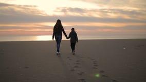 A mamã e seu filho estão andando ao longo do litoral no por do sol filme
