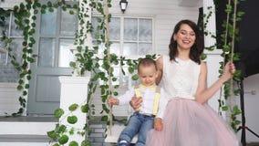 A mamã e seu filho montam em um balanço perto da casa vídeos de arquivo