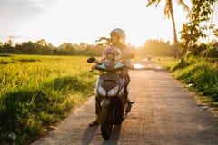 A mamã e sua criança apreciam montar o 'trotinette' da motocicleta fotografia de stock
