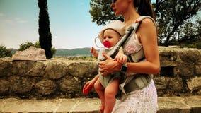 A mamã e sua criança que viajam com portador de bebê backpack em férias video estoque