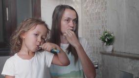 A mamã e sua filha pequena bonito estão escovando os dentes com escovas de dentes junto vídeos de arquivo