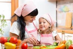 Mamã e sua filha que preparam vegetais na cozinha Imagem de Stock