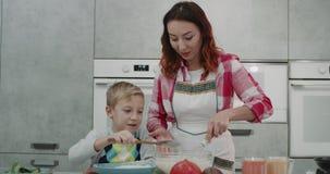 Mamã e sua preparação do filho panquecas junto na manhã para o café da manhã em uma cozinha moderna vídeos de arquivo