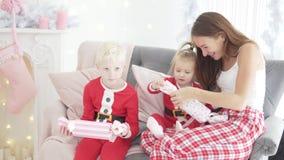 A mamã e suas crianças abrem presentes de Natal vídeos de arquivo