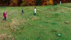 A mamã e suas crianças jogam-nos com a bola na floresta do outono corrida do divertimento e jogam-se uma bola A família é filme