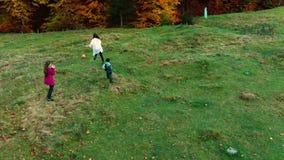 A mamã e suas crianças jogam-nos com a bola na floresta do outono corrida do divertimento e jogam-se uma bola A família é video estoque