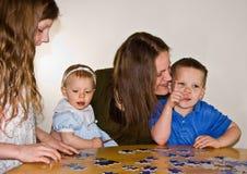Mamã e três miúdos que fazem um enigma Fotografia de Stock Royalty Free