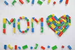 MAMÃ e um coração com blocos de madeira coloridos do brinquedo imagem de stock royalty free