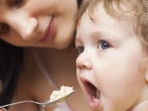 Minha mãe está alimentando um papa de aveia pequeno da criança com uma colher Imagens de Stock