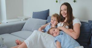 A mamã em um vestido e as jovens crianças sentam-se no sofá e olham-se sua série de televisão favorita filme