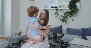 Mamã em um vestido que senta-se no diwanie que abraça seu filho