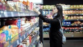A mamã em uma prateleira do supermercado escolhe o alimento para seu filho filme