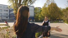A mamã encontra perto da escola uma filha adolescente após a escola Menina 13 anos velha na farda da escola fora da escola video estoque