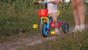 A mamã ensina a filha montar uma bicicleta Close-up Jogos da mãe com sua filha pequena uma criança pequena aprende montar a