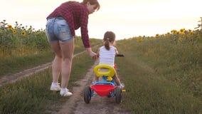 A mamã ensina a filha montar uma bicicleta em uma estrada secundária em um campo dos girassóis Uma criança pequena aprende montar