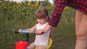A mamã ensina a filha montar uma bicicleta Jogos da mãe com sua filha pequena uma criança pequena aprende montar uma bicicleta Co