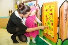 A mamã ensina sua criança da filha às figuras na sala de jogos. Fotografia de Stock